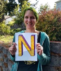 "Nicole Hoover smiling and standing outside a gray brick wall in front of bushes holding a colorful yellow and purple letter ""N"" in block font on a white piece of paper. She has green hair, a teal coat and black shirt"