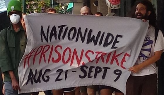 protesters holding prison strike banner