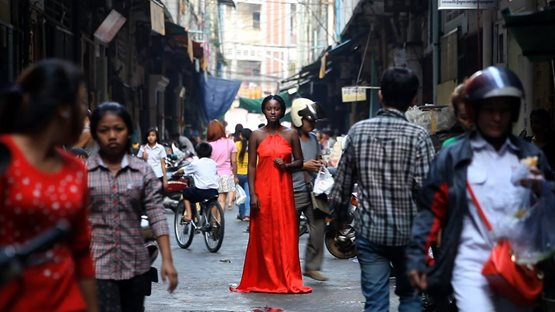 image of woman in red dress on busy street from Neon Poem