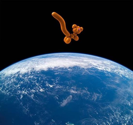 """Number Nine,"" archival pigment print by Barbara Noah, shows a balloon cat, representative of feline species threatened by climate change, floating over Earth."