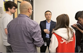 Bellevue IT manager Enzhou Wang discusses project with students.