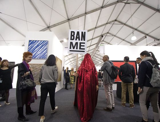 "photo of the Red Chador holding a ""Ban Me"" sign while walking among people"