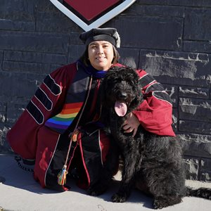Image Description: Academic Success Coach, Dr. Paulina Abustan, wearing their WSU Ph.D. graduation regalia and rainbow pride stole, smiling, with their black access labradoodle puppy, Meelo.