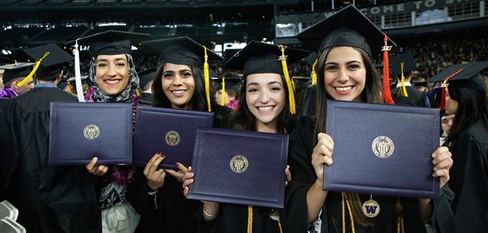 Four female students stand in graduation cap and gown holding their diplomas