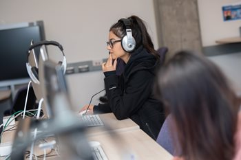 A woman in a computer lab with headphones looking at a computer