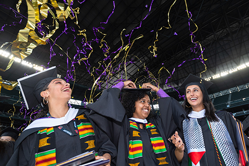 Graduates at commencement as streamers come down from ceiling