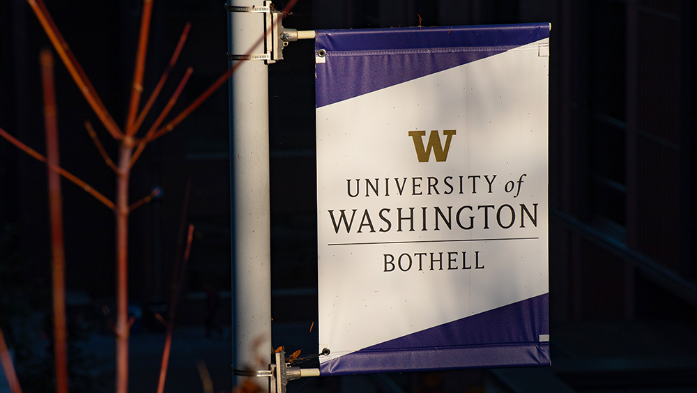 UW Bothell campus banner hanging on a post with red trees in front of it.