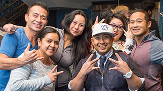 Group of alumni making the W sign with their hands