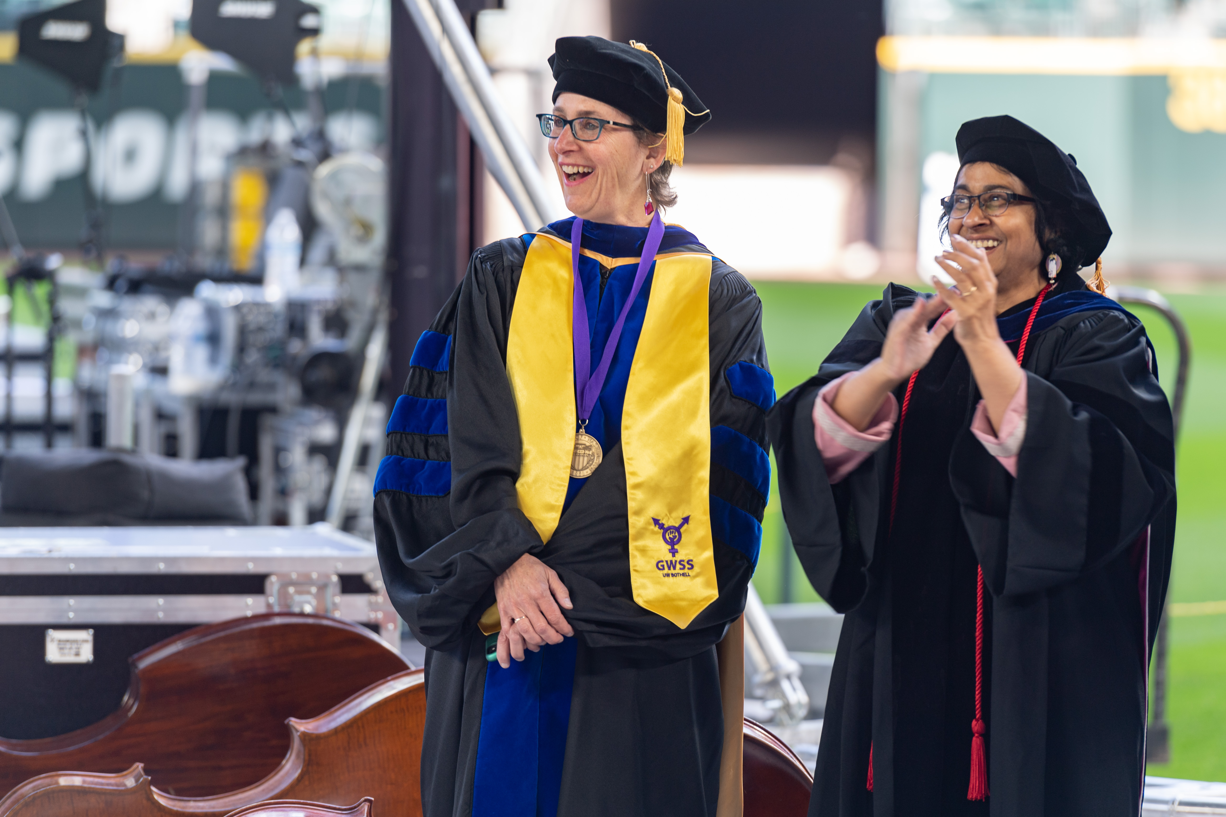 Two people, one wearing a stole, participate in commencement