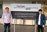 Brent Lagesse and Kevin Wu by PerCom 2019 sign