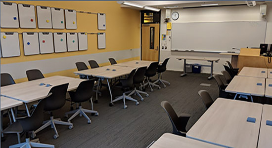 UW1-060 classroom set in the default group format and showing gold accent wall and personal whiteboards