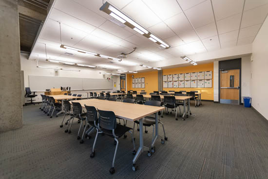 UW1-202 classroom set in the default group format and showing gold accent wall and personal whiteboards