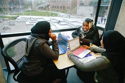 three students on their laptops in the UW Bothell library smiling