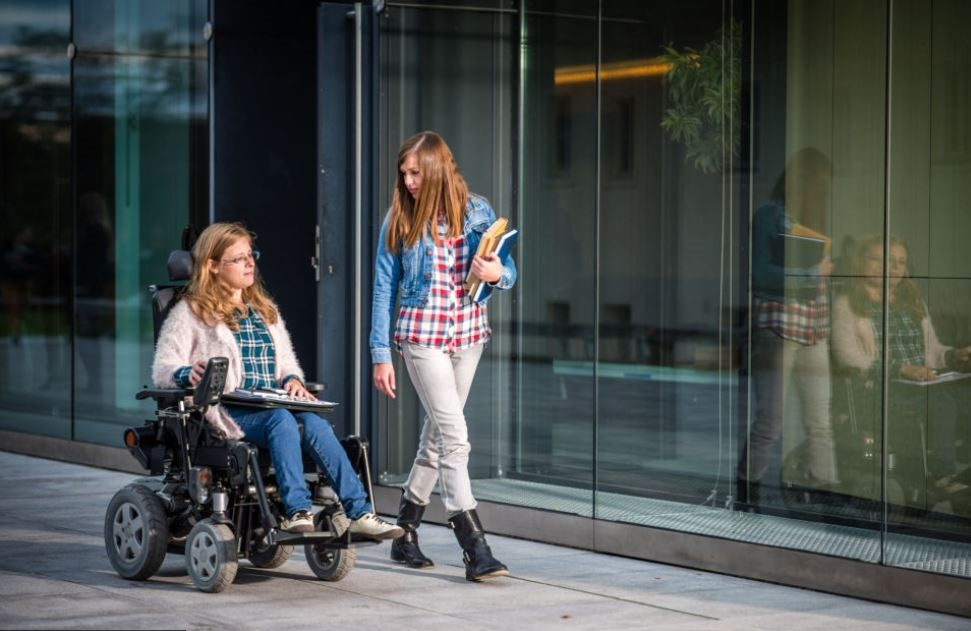 two people talking, one is in a wheelchair and the other standing and walking along side them.