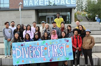 group of first generation students on the plaza holding a sign saying diverse first