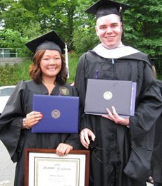 Hillary and Peter, at graduation holding their diplomas.