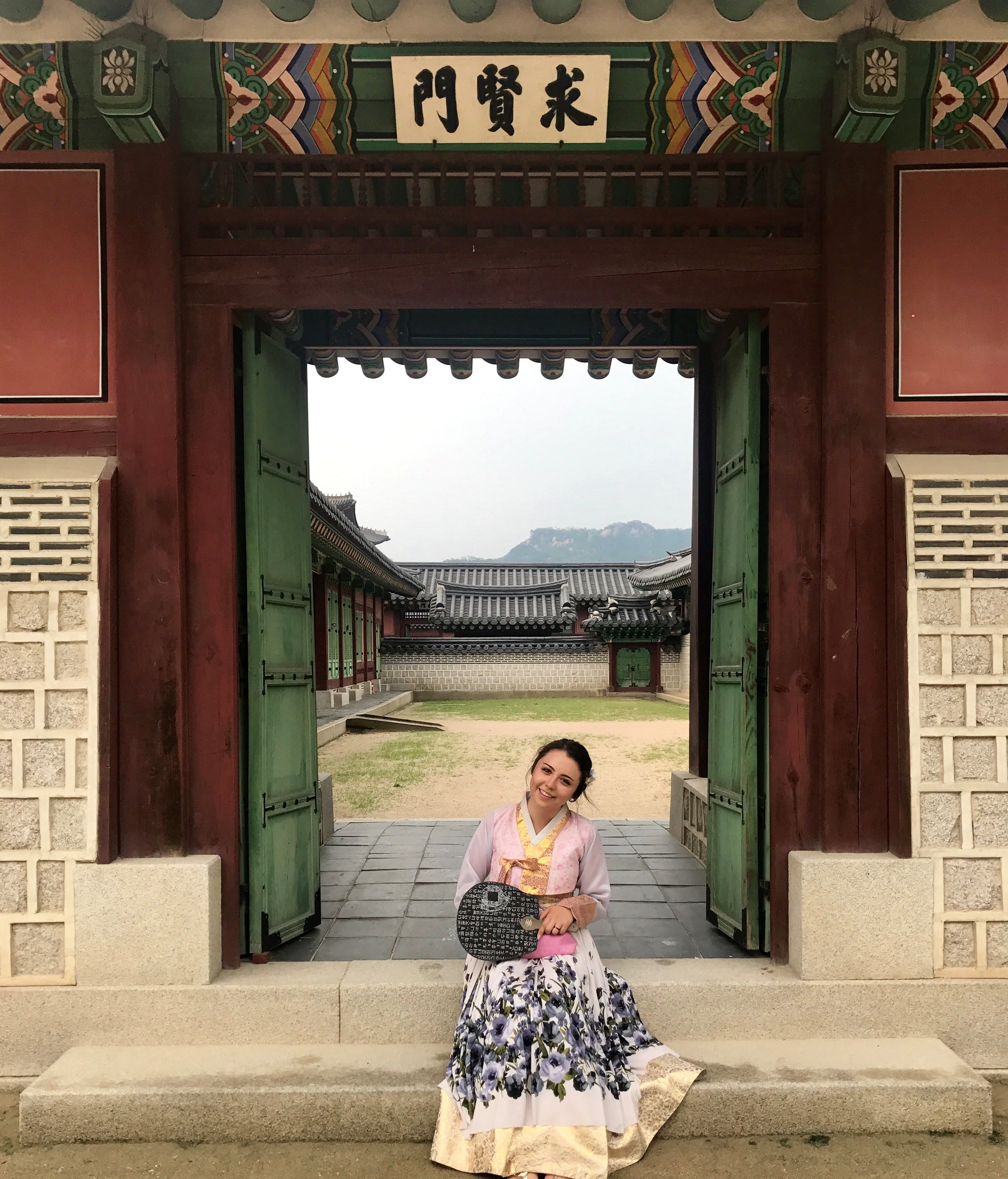 Student, Elaine Montes sitting in front of an Asian temple dressed in a traditional Korean Hanbok.