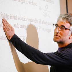 male professor standing in front of a projector screen with information displayed that he is pointing out