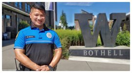 Officer Rodel Cruz Naval on campus in front of the W statue