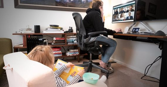 Person working at home with child.