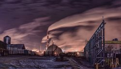 Industrial pollution darkens sky.