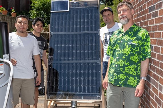 Students with solar heater and sponsor.