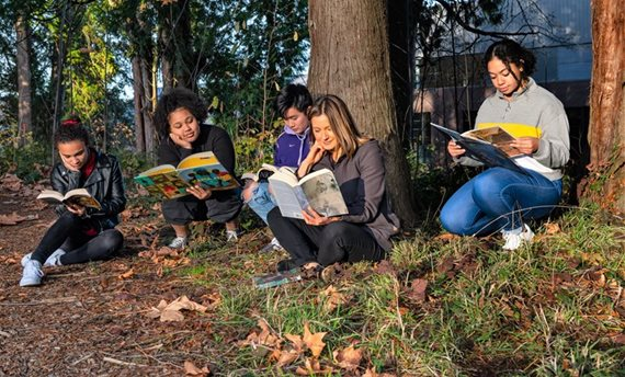 Students with books in forest.