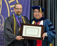 McRae receiving Chancellor's Medal from Kenyon Chan in 2012.