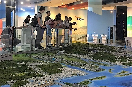 Students look at model of Busan.