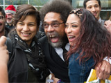 Cornel West laughing and posing with two students