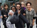 Cornel West laughing and posing with a small group of students and staff