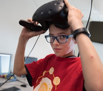 student holding virtual reality goggles on head