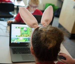 student wearing bunny ears looking at laptop