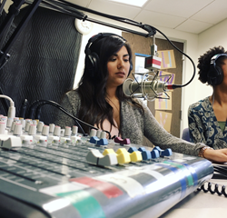 UWave Radio participants in broadcasting studio, wearing headphones while speaking into a microphone