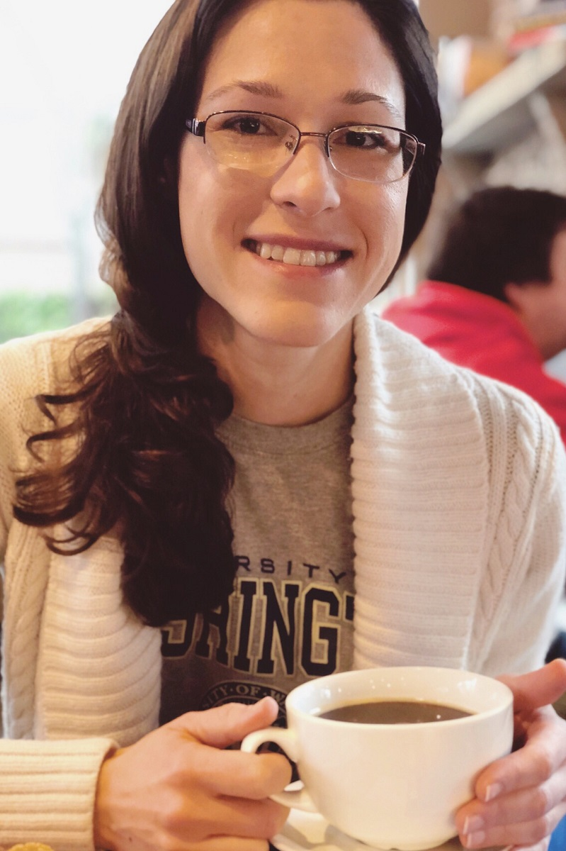 Photo of Rachel Gridley-Waters, smiling and holding a coffee cup.